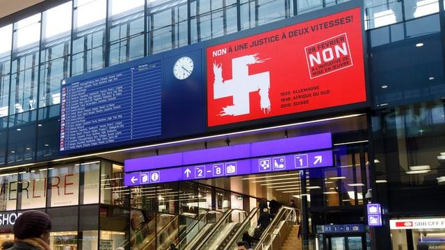 Hakenkreuz-Plakat auf der Werbefläche der Abfahrtstabelle (eBoard) im SBB-Bahnhof Genève.