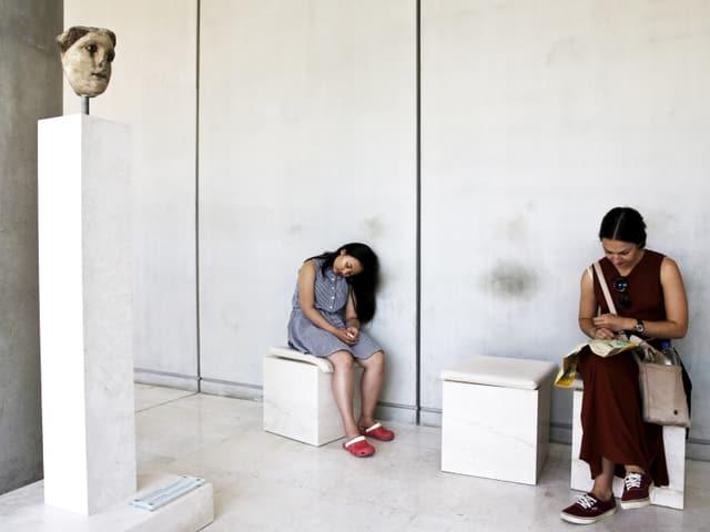 Zwei Besucherinnen ruhen sich auf Hockern aus, neben einer antiken Statue.