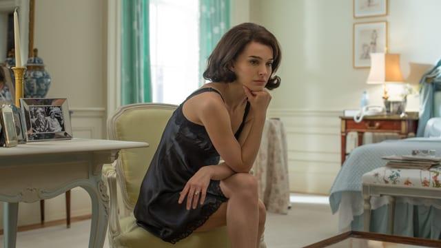 Nathalie Portman sitzt als Jackie in einem Nachthemd in ihrem Zimmer.