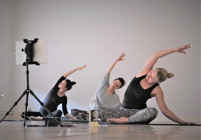 Drei Frauen machen Yogaübungen vor einer Kamera