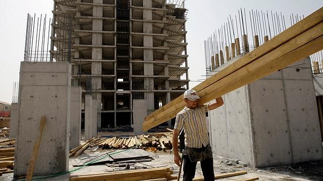 Ein Arbeiter trägt einen grossen Balken über eine der zahlreichen Baustellen in Erbil.