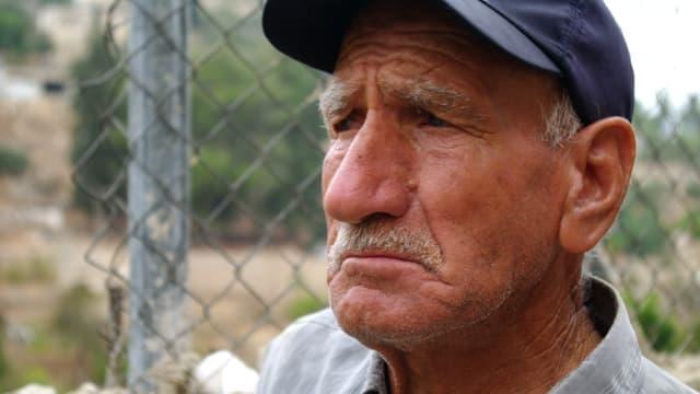 Ein älterer Mann mit Oberlippenbart und Dachkappe, leicht traurig und verbittert in die Ferne schauend.