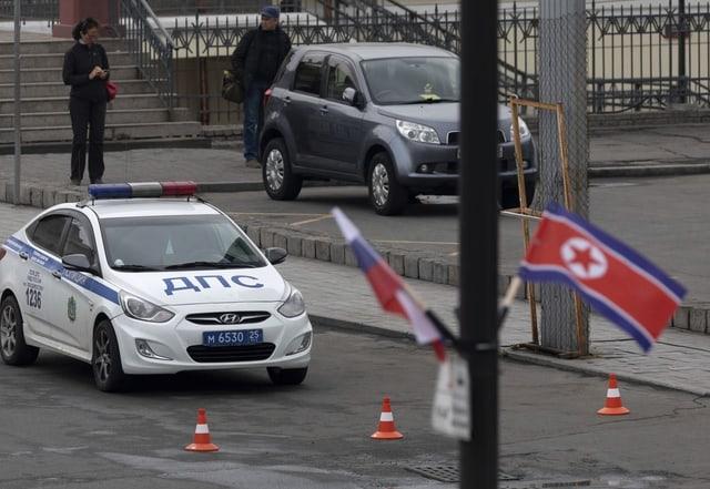 Zwei Flaggen, dahinter ein Polizeiauto