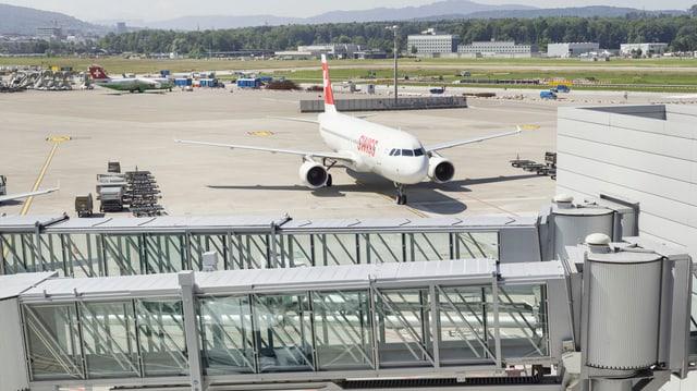 Ein Flugzeug der Swiss steht parkiert auf dem Flughafen Zürich, im Vordergrund