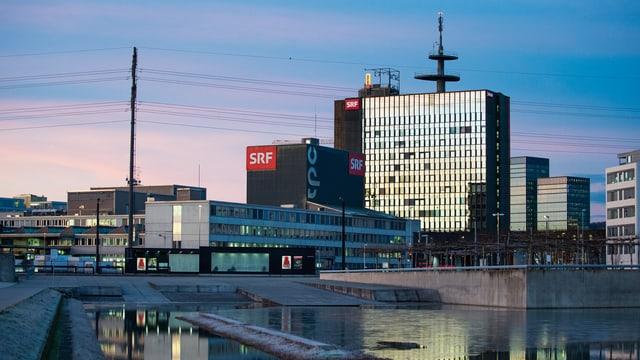 Zu sehen ist das SRF-Hochhaus in Leutschenbach im Morgenrot. Das SRF-Logo prangt markant von der Fassade. Im Hintergrund sind Hochspannungsleitungen zu sehen.