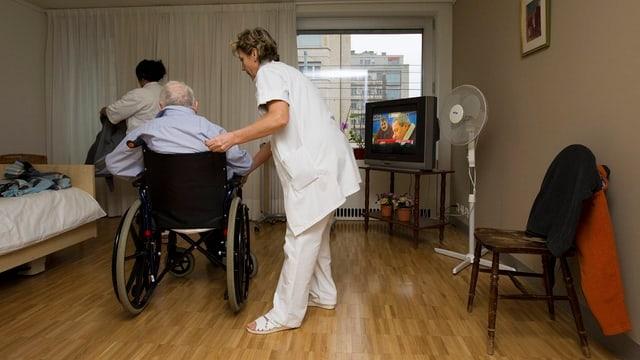 Eine Pflegerin hilft einem alten Mann im Rollstuhl