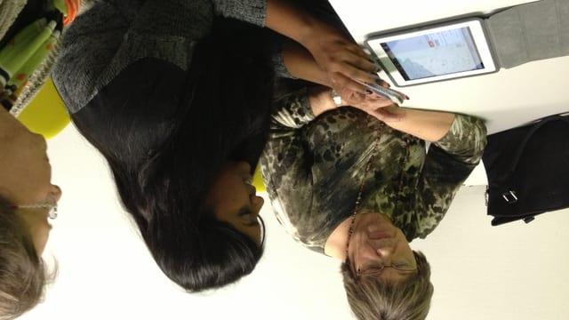 Eine Jugendliche des St. Galler Motivationssemesters zeigt zwei Seniorinnen, wie man Apps auf einem Tablet-Computer anwendet.
