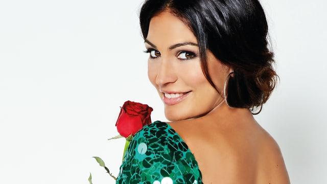 Eine Frau lächelt über ihre Schulter in die Kamera. Sie trägt ein rückenfreies grünes Kleid und hält eine Rose in der Hand.
