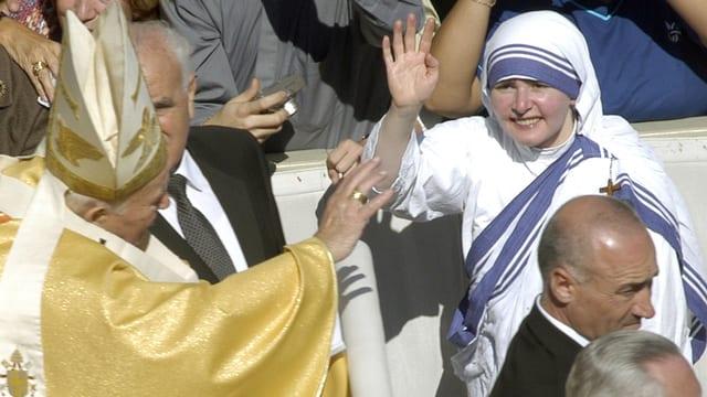 Papst Johannes Paul II. winkt einer Ordensschwester.