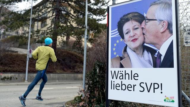 Ein Jogger rennt an einem SVP-Plakat vorbei, darauf das Bild von Juncker, wie er Sommaruga küsst.