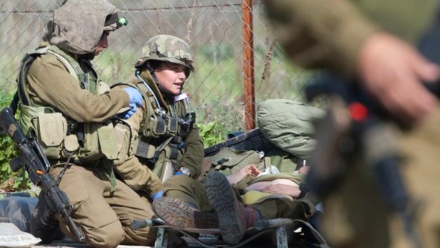 Ein verwundeter israelischer Soldat wird von seinen Kameraden versorgt