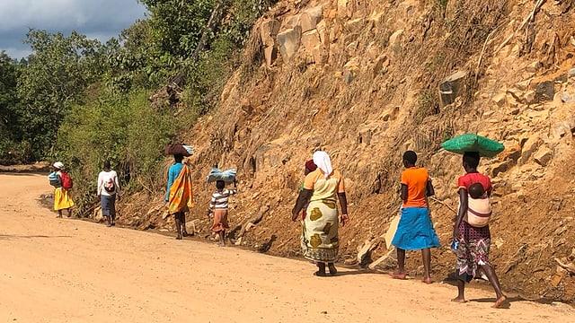 Eine Gruppe von Frauen und Kindern geht einer Strasse entlang und trägt erhaltene Moskitonetze