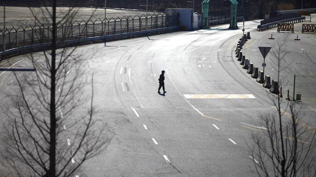 Ein einsamer Mann auf der breiten Verbindungsstrasse zwischen dem Industrie-Komplex von Kaesong und der Grenze zu Südkorea.