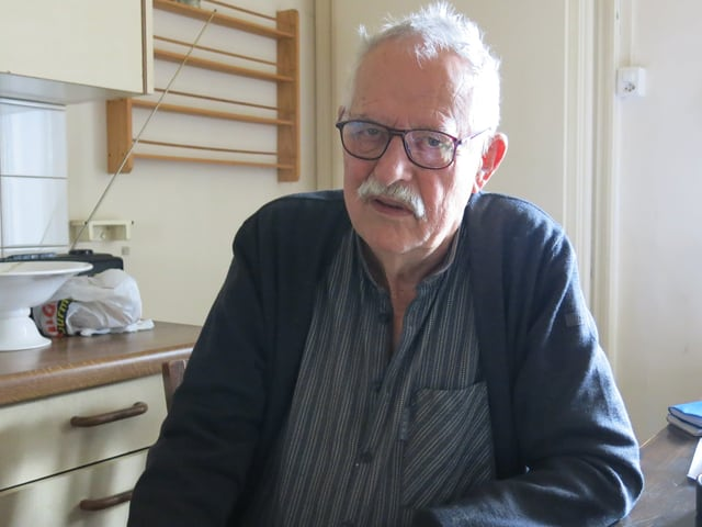 Hansjörg Schneider sitzt am Küchentisch und schaut ernst in die Kamera.