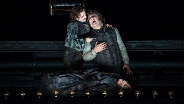 Ein Mann hält einen anderen Sänger auf einer dunklen Bühne im Arm.
