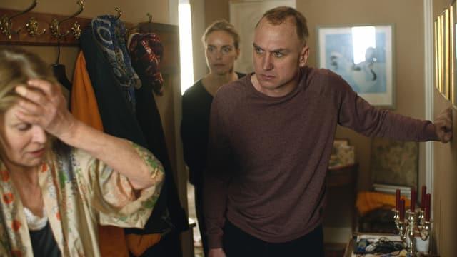 Filmstill: EIn junger Mann und eine junge Frau blicken auf eine ältere Frau, die sich an den Kopf greift.