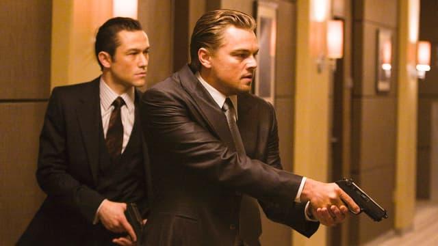 Zwei Männer im Anzug mit Pistolen.