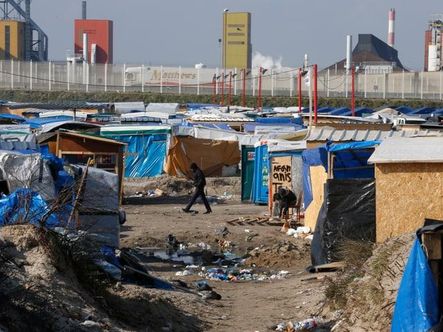 Zelte und Bretterverschläge auf offenem Gelände.
