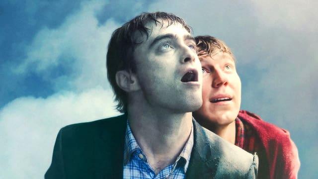 Zwei junge Männer blicken gegen den Himmel.