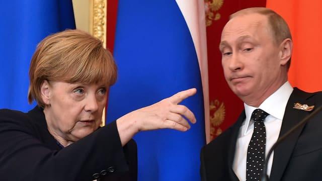 Angela Merkel zeigt mit dem Finger, Wladimir Putin macht ein betretenes Gesicht.