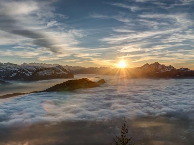 Berglandschaft mit einigen Hügeln und Gipfeln. Die Täler sind mit Nebel gefüllt. Darüber geht die Sonne gerade am Horizont unter.