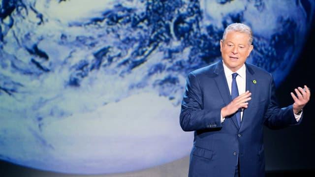 Al Gore steht vor einer riesigen Projektion der Erde.