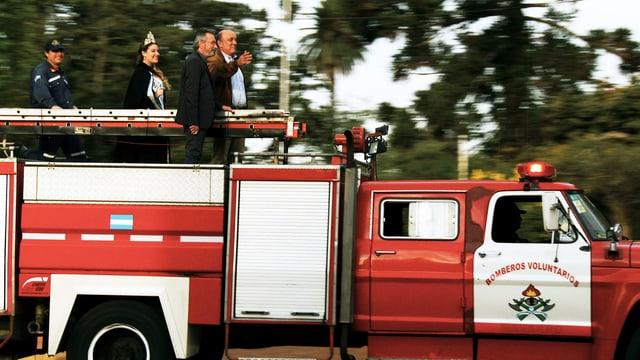 Feuerwehrauto mit Menschen drauf.
