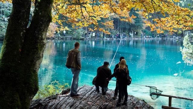 Gruppe von Leuten am Ufer des Blausees, eine Person mit Angel in der Hand.