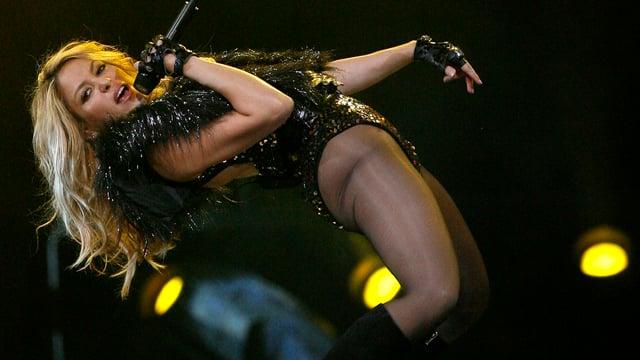 Shakira im schwarzen Bühnenoutfit während einem Konzert.