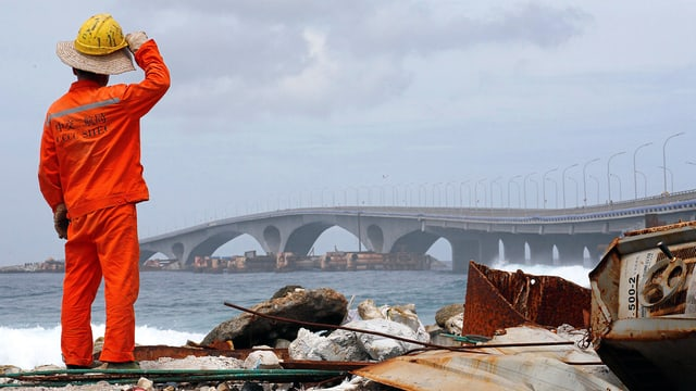 Ein Arbeiter in orangem Gewand steht vor der Brücke in der Ferne.