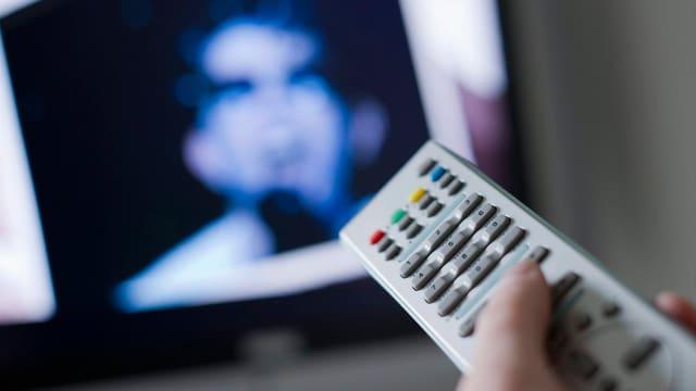 Jemand hält eine Fernbedienung in Richtung eines Fernsehbildschirms, auf dem jemand singt.