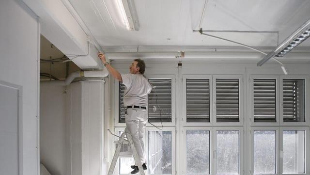 Ein Maler steht auf einer Leiter und streicht eine Wand.