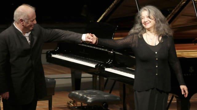 Daniel Barenboim und Martha Argerich stehen vor einem Piano und halten die Hand.