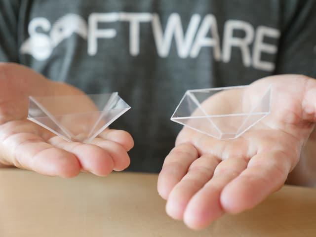 Ein Mann präsentiert zwei selbst gebastelte Hologramm-Projektoren.