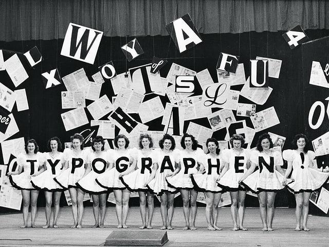 12 Ballettänzerinnen posieren auf der Bühne mit je einem Buchstaben auf dem Kleid. Es ergibt sich das Wort «Typographen» mit Ausrufezeichen.