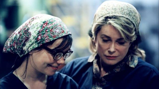 Zwei Fabrikarbeiterinnen mit Kopftuch, die eine lächelt.