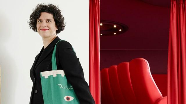Eine jüngere Frau steht vor dem Eingang zu einem Kinosaal, der mit roten Sesseln bestückt ist.