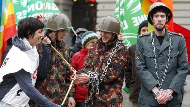 Mitglieder des Initiativkomitees stehen wäehrend einer Aktion mit Militäerkleidung und Ketten auf dem Bundesplatz.