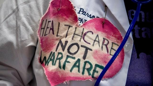 Purtret d'in cor cun scrit «Healthcare not warefare», quai che munta «provediment medicinal, nagina guerra».