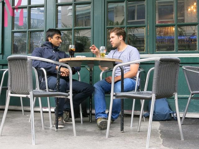 An einem Tisch vor einer Bar sitzen zwei Männer und unterhalten sich.