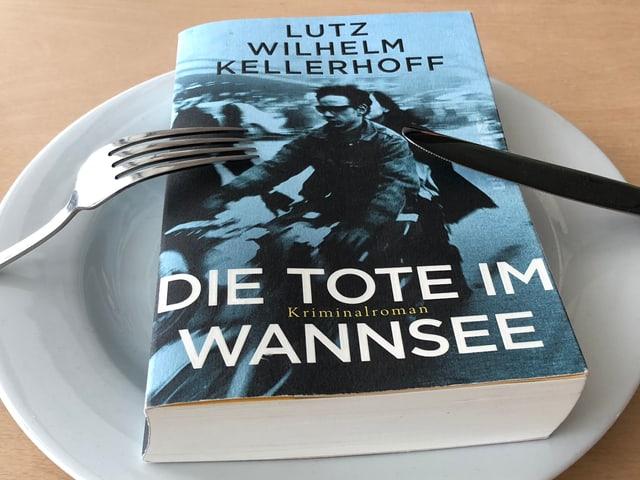 «Die Tote im Wannsee» liegt auf einem weissen Teller, Messer und Gabel seitlich an den Teller gestellt