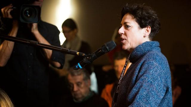Eine Frau im blauen Pullover steht vor einem Mikrofon uns spricht.