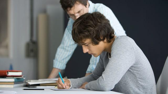 Lehrer schaut einem schreibenden Schüler über die Schulter.