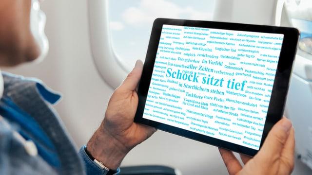 Ein Mann hält in einem Flugzeug ein Tablet, auf dem viele blaue Wörter in Form einer Wolke dargestellt sind