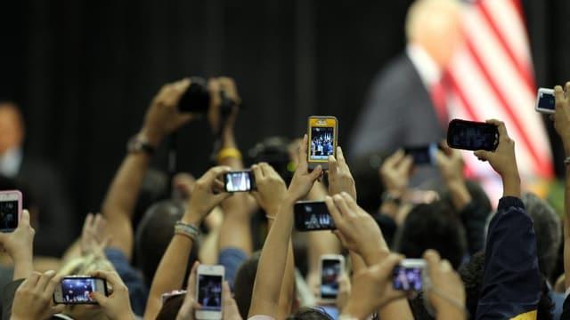 Mehrere Handybesitzer fotografieren gleichzeitig mit ihrem Handy ein Objekt, das nicht ersichtlich ist.