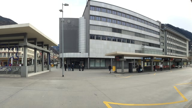 L'edifizi grisch da l'anteriur Globus a la staziun da Cuira, davant ves'ins la staziun da bus.