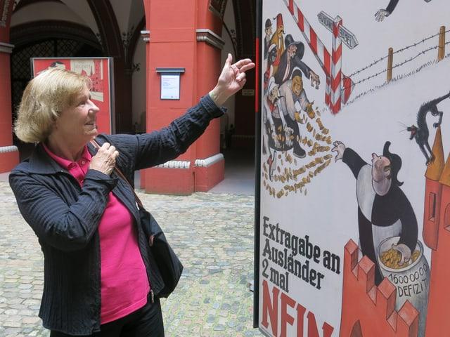 Eine Frau zeigt auf ein Plakat.