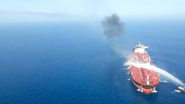 Roter Öltanker im blauen Meer wird mit Wassers aus Löschschiffen besprüht.