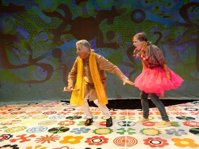 Szenenbild: Mann und junge Frau, Blumentapete am Boden