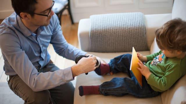 Vater zieht seinem Sohn die Schuhe an